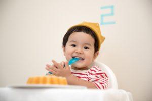 Beikosteinführung: Kind sitzt im Hochstuhl, isst und lacht