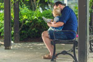 Papa liest mit Kind im Park