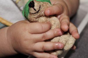 Kind hält einen Teddybären in der Hand
